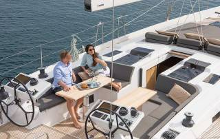 couple relaxing sunbathing in cockpit luxury sailing yacht charter