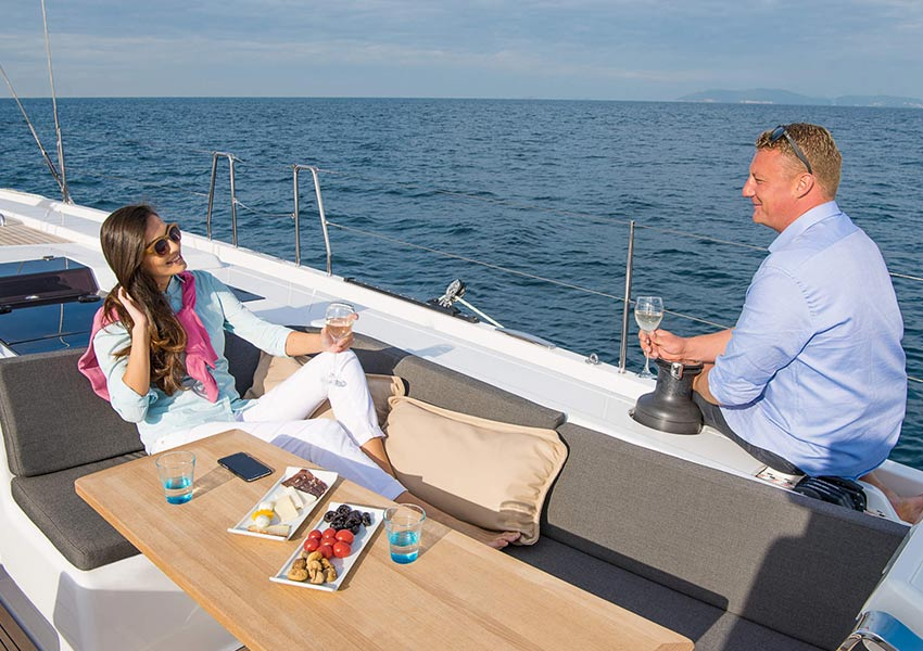 yacht charter italy bareboat married couple enjoying sun and glass of prosecco in cockpit of the yacht